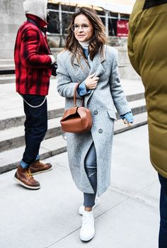 A long gray coat is worn over a denim jacket with a tan bag, skinny jeans, and white sneakers