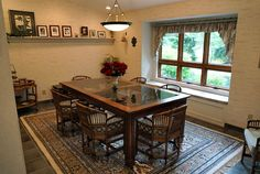 Dining room with white walls, window seat, wood and glass table.
