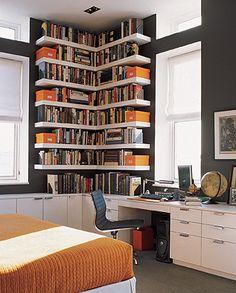 bonito o contraste da parede escura com os móveis, prateleiras e moldura brancos e o colorido dos livros e caixas nas prateleiras.