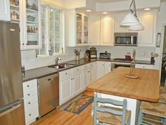 Spacious upgraded kitchen with stainless appliances, hardwood floor, granite countertops and butcher block center island with breakfast bar