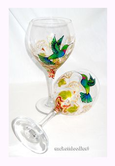 Made To Order Hummingbird Wine goblets areArt on glass customized hand painted glassware design. Each hand painted glass is designed with a blue and green designed hummingbird lingering over flower bl