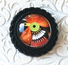 Schwarze Brosche aus Kunststoff mit einem Hahnmotiv in leuchtenden Farben. Auf der Rückseite sitzt eine silberfarbene Anstecknadel..