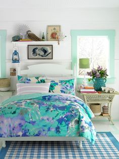 Modern bedding designs for 2015. Blue, green, and purple floral watercolor bedding motif with light sea foam green wall color and nautical decor