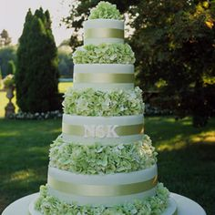 Tiered Wedding Cake with Monogram  A traditional tiered confection covered with pale green fondant has fresh hydrangeas between the layers (each cake tier is topped with clear acetate so flowers don't touch the icing). The monogram is made of royal icing sprinkled with nonpareils for texture.