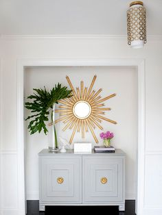 Make a Statement  Who says storage can't be stylish? With the doors removed, an unused coat closet makes a striking style statement in this chic entryway. An old sideboard, given new life with a fresh coat of gray paint and decorative doorknobs, offers concealed storage for a variety of seasonal items. A sunburst mirror above the unit commands attention and creates a dramatic focal point.