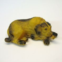 """What a great and very unusual vintage figural dog tape measure! Measuring 1 1/2"""" by 3 3/4"""". this large laying down dog has his tongue out which is the measure itself. Made of some kind of slightly harder celluloid he is in fine original condition with no damage. Dates to around the 20's or 30's.  Quirky Antiques on  Ruby Lane."""