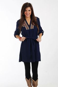 """The Aimee Dress, Navy $42.50  We are loving this cute little dress! The silky navy shift dress has tribal embroidery around the neckline, tabbed sleeves and a sash to tie in the waist for the most flattering fit! Throw this on with cowboy boots for a look that's right on trend.   Fits true to size. Miranda is wearing a small.   From shoulder to hem:  Small - 33""""  Medium - 34""""  Large - 35"""""""