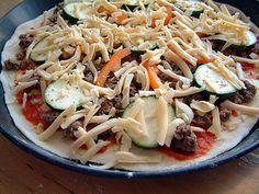 Auf den Pizzateig: Pizzasoße, Hackfleisch, Gemüse und dann Käse