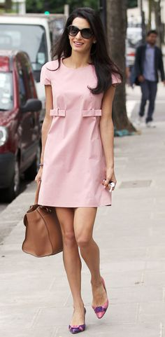 Out and about in London, Amal was pretty in pink while dressed in a bow-adorned frock with matching raspberry and violet pumps and chic accessories.