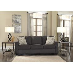 Incorporate trendy design into your living room with the Alenya sofa by Ashley Furniture. Charcoal grey fabric upholstery gives this piece subtle, unassuming style, while two included script-pattern throw pillows add vintage charm.