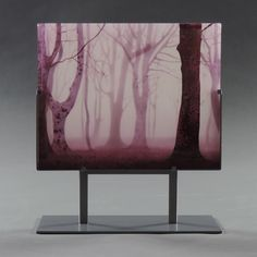 Misty Morning by Paul Messink. This kiln-worked glass panel is hand painted, using enamel, on individual layers of glass. When all the layers are complete, they are stacked in a kiln and fused into a solid panel. Multiple layers give the work incredible depth and dimension. This panel is made from nine layers of glass and is over 1'' thick. It is displayed in a metal gallery stand, which is included with your purchase. Dimensions listed include the base. While this piece looks great o...