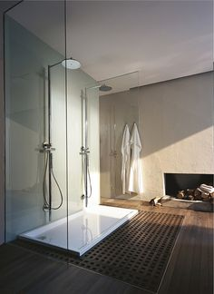 Modern Chic Bathroom. Love the Double Showers, wood floor & the fireplace.