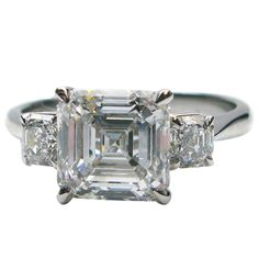 2.50 Carat Asscher Cut GIA Cert Diamond Platinum Three Stone Engagement Ring | From a unique collection of vintage engagement rings at https://www.1stdibs.com/jewelry/rings/engagement-rings/