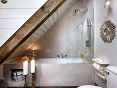 Floral tile was replaced with acres of slick Caesarstone wrapped across the main wall areas and around a deep soaker tub. A rain head shower features high pressure jets, while fixed glazing protects the room from water splash.   - CountryLiving.com
