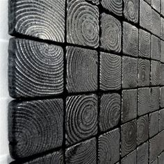 For this wall sculpture square slices of red cedar have been blackened and charred in a controlled burning process. Each piece of charred wood has been carefully attached to a blackened birch backboard.
