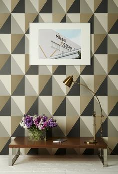 Apex Grand Wallpaper A bold and modern wallpaper with a geometric motif of interlocking triangles, shown in shades of grey, beige and metallic gold.