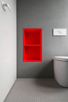 Karhard architektur & design // grey bathroom with ref built in shelf ; Orange. Red. Shelving. Pop. Color. Bathroom. Tiles. Design.