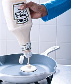 Clean out a ketchup bottle and add your pancake batter. This will allow you to squeeze out as much as you want without dealing with all the mess. This would also work great with mustard and honey bottles, or any other squeezable bottles.