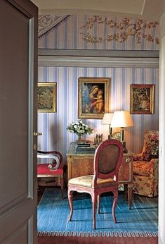 Mlinaric and Henry extended the 19th-century stripe down the walls of the study. The painting is flanked by a pair of French tapestries. On the Louis XVI-style mahogany desk are two tole oil lamps, which were electrified. The painted side chair is Italian.