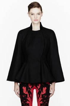 ALEXANDER MCQUEEN Black Light Felt Cape Jacket: Flared sleeve felted wool cape jacket in black. Stand collar in tonal velvet. Button fly front with curved accent placket. Flared peplum detail at waist. Split at interior sleeves stitched at back creating cape effect. Partially lined. Tonal stitching. Made in Italy.