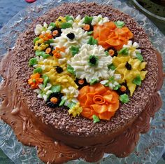 2-layer chocolate cooked icing dripping over sides of cake with chocolate shavings on top and buttercream icing flowers.