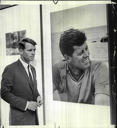 Bobby Kennedy stands beside a large photo of his brother, Jack.