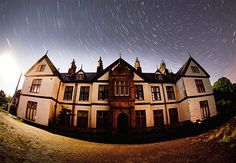 A wide-angle lens captures a big English house and star trails above it.