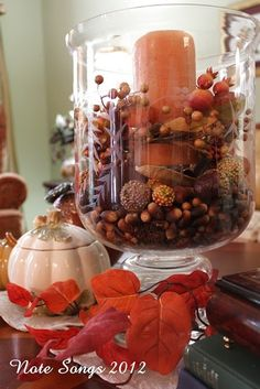 """I actually went out in my front yard and picked up some little acorns from the oak trees and poked them into this big vase and then continued adding my little decorative things ending with a candle and a little candle ring""..."