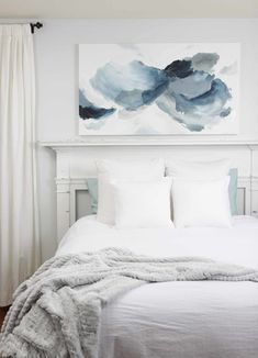 """I absolutely love this 30"""" X 54"""" abstract painting in soft and soothing blue and grey tones in this minimal bedroom. There is nothing like all white and neutral bedding and linens with abstract artwork adding some color and dimension to the room. This piece of art was made custom to go above a bed and completes this bedroom interior space perfectly above this unique white fireplace mantle headboard. Learn more about commission pricing & the process to order a custom painting from Deeann…"""