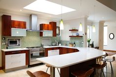HOUSE DURBANVILLE BY JOOS  This inviting contemporary kitchen combines wood and glass with a Caesarstone-topped breakfast nook and a fun green mosaic splashback. Note the novel built-in bread bin. #DESIGNER #KITCHENS