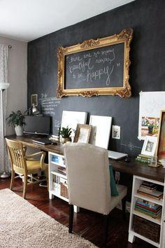 home office com dois lugares, parede com tinta lousa e moldura dourada grande na parede