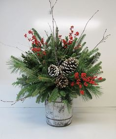 small barrel arrangement with evergreens, pinecones and berries