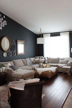 la tendance hygge deco scandinave pour un intérieur cocooning qui invite à la détente, salon blanc et noir avec des cadres déco vintage et un grand canapé d'angle accueillant