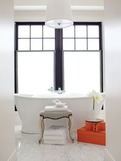 A freestanding cast-iron tub is perfectly centred beneath a wide double window in the principal ensuite. The floors are heated Calacatta marble. An ornate 18th-century Italian stool looks spa-fresh covered in a striped seersucker fabric. Donghia stool fabric. Hermes touch... I am IN LOVE!