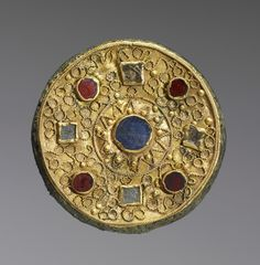 A disk brooch ornamented with filigree sun design. Crafted out of gilded bronze, glass, and stones. Made in the 600s for a Merovingian Frankish nobleman in northern Gaul (along the Rhineland). Currently on view at the Walters Art Museum.