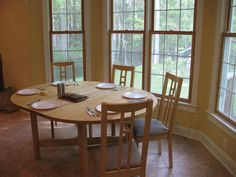 Kitchen:Round Wooden Dining Table Wooden Dining Chairs With Linen Seat Glass Window Stone Flooring White Plates Stainless Steel Spoon The Simple Kitchen Tables and Chairs