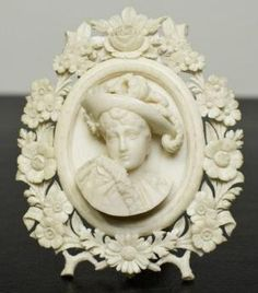 Victorian High Relief Carved Ivory Cameo with Carved Floral Frame.  This is most likely an Austrian or German origin based on her dressing, feathered hat, and its decorative frame. The frame itself is a work of art, carved with rose, lily of the vally, forget-me-not, daisy, and acorn leaves.