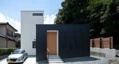 White smooth stucco for addition, black stucco for existing house