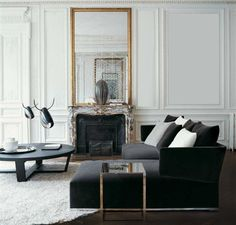 Stunning and very luxurious black velvet sofa. The golden side table and the golden wall mirrow are the master pieces of this ambience