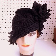 Relive the 1920s style. Wear this LAUREN crochet cloche hat for women in black cotton. Set the mood and elegance. The measurements are 9in(23cm) high and 23in(59cm) when stretched. No need for clasps nor ties. It cups the head and fits over the ears. The pointy edge asymmetrical brim extends to one side and will not fall in your face. Change the style with one turn. The matching zigzag 3 inch wide flower and textured leaf compliment each other. Feel comfortable. This depends on the head…