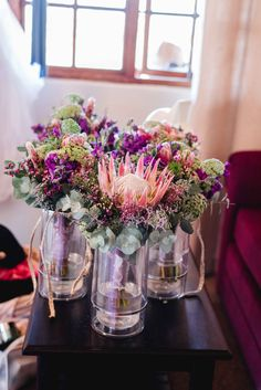 Proteas and penny gum love. Pink, purple and guinea fowl feathers Bridesmaid Bouquet, Bridesmaids, Guinea Fowl, Pink Purple, Feathers, Bouquets, Glass Vase, Wedding Day, Table Decorations