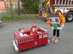 Cardboard firetruck over wagon, firedog, firefighter, and house on fire costumes.