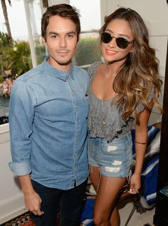 Actors Tyler Blackburn (L) and Shay Mitchell attend the Hollister House on August 3, 2014 in Santa Monica, California. #prom #necklace