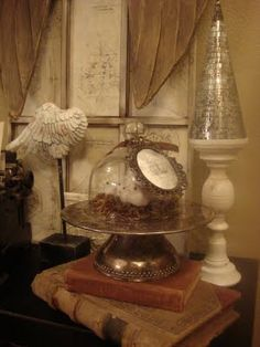 Dollar store mirrored conical trees antiqued and glued on candle stick.  Dollar store birdies under a glass cloche. Frame with paintable wallpaper. Frame - paper aged wit coffee and stamped with musical note stamp. Rough up some thrift store books. No tutorial, but easily DIY.