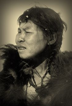 Chukchi woman with three fertility tattoos on cheek and a cruciform tattoo foil marking the corner of her mouth that was intended as a charm against evil spirits. Foils were also stitched into living skin if the individual had been in great danger and had escaped. Photograph ca. 1900.  From Shamanic Skin: The Art of Magical Tattoos | Lars Krutak