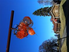 Indigo, a glassblowing workshop in Sarpsborg. A cluster of orange glassbubbles make magic against the blue sky.