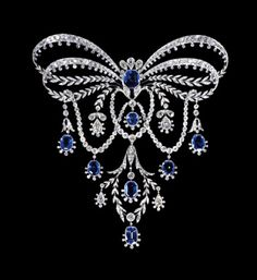 Platinum & gold bow knot stomacher brooch, the ribbons in two loops each divided into a line of diamonds edged with sparks, & lines of stylised laurel meeting at a centre octagonal sapphire surmounted by three pear shaped diamonds, & with laurel leaves terminating in three pear shaped diamonds on each side of the festoon below, & terminating in a laurel wreath with one sapphire within & another at the base, & two pear shaped diamond drops to each side.