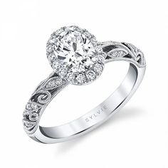 This stunning vintage oval engagement ring features a 1.25 carat oval diamond center in our signature halo. The band itself features intricate milgrain accented filigree swirls that cascade down both sides of the diamond encrusted shank for a total weight of .37 carats. This ring is available in 14k, 18k, rose, white or yellow gold as well as platinum and can be made in eternity style. Vintage Oval Engagement Ring | 1.25 Carat Oval Diamond Engagement Rings | Sylvie Collection Vintage Oval Engagement Rings, Double Halo Engagement Ring, Perfect Engagement Ring, Diamond Engagement Rings, Thing 1, Oval Rings, Oval Diamond, Wedding Bands, Gold