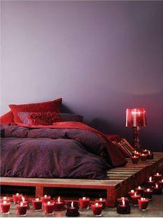Ambiance romantique dans la chambre avec des palettes bois pour accueillir le matelas et la lampe de chevet