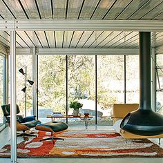 Think spare - Get a Mid-Century Modern Look - The glass walls aren't the only reason this living room feels like a retreat. The minimal furnishings—with their clean, mid-century modern lines—and the floating fireplace create a sense of openness.
